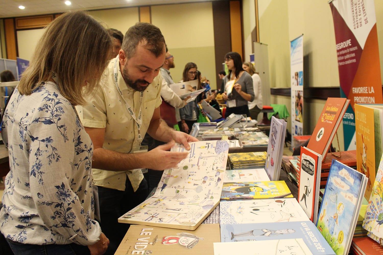 Deux personnes regardent un document à un kiosque dans un évènement