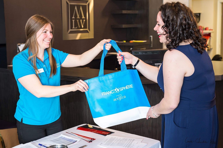 Une organisatrice d'évènement remet un sac promotionnel à une participante