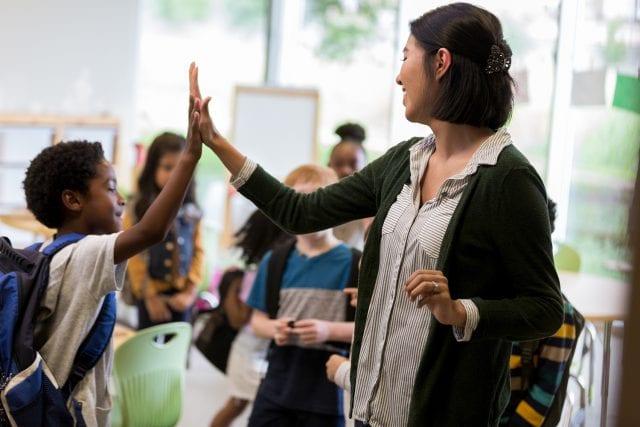 Enseignante et jeune qui se tapent dans la main