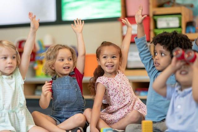 Jeunes enfants assis en cercle au sol, levant la main