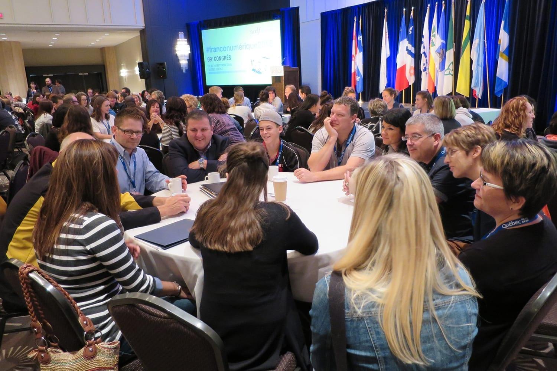 Gens de plusieurs âges discutant ensemble autour d'une table dans une salle de réception
