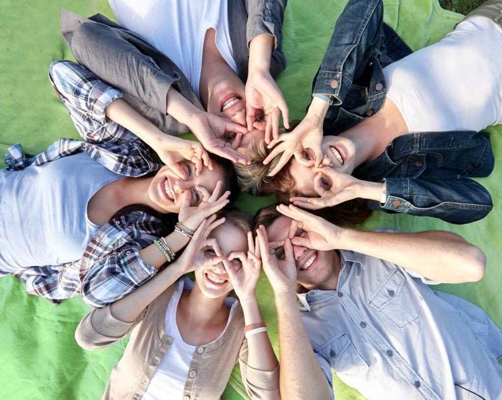 Adolescents couchés en cercle faisant des lunettes avec leurs doigts
