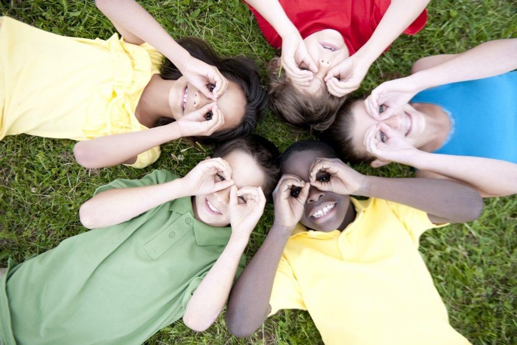 Enfants couchés en cercle faisant des lunettes avec leurs doigts