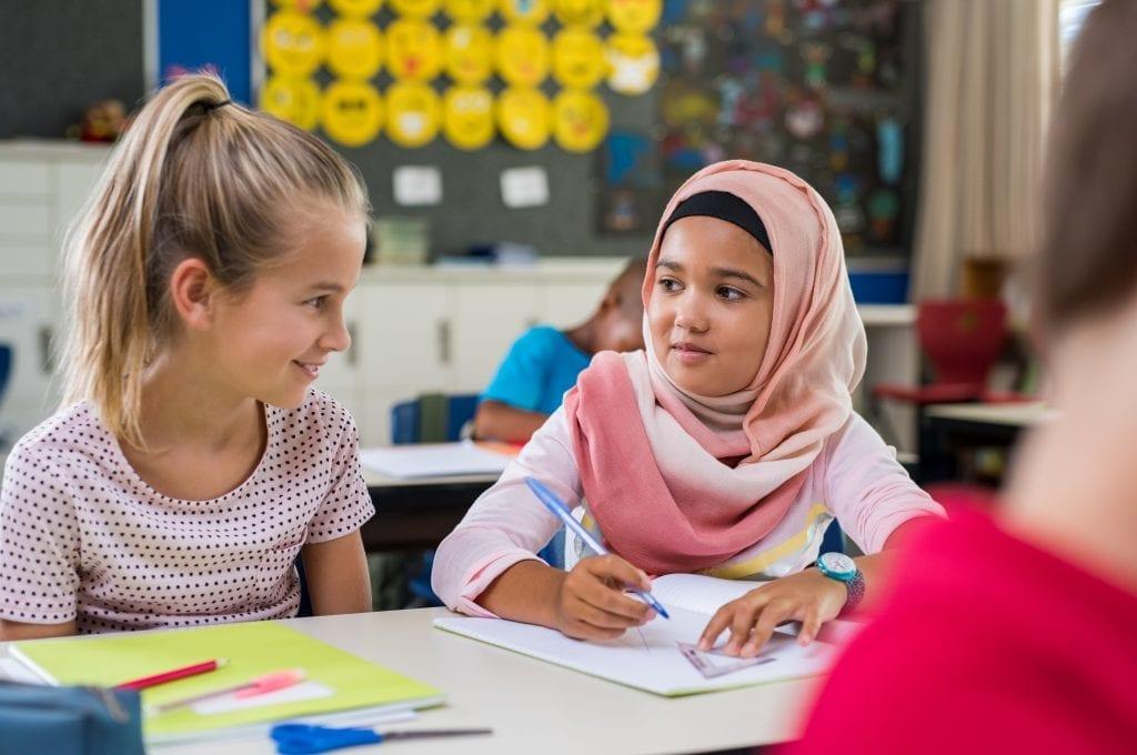 Deux élèves qui discutent dans une classe