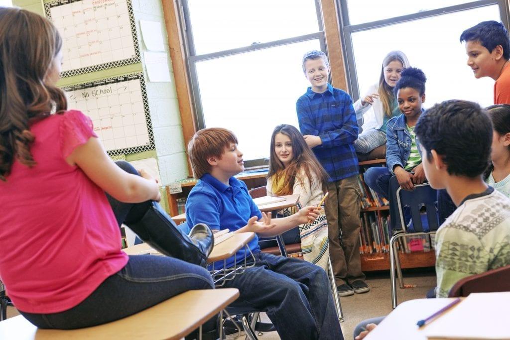 Groupe d'élèves du primaire dans une classe qui discutent