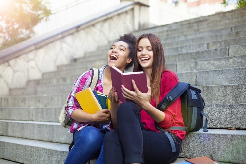 Deux adolescentes qui rient en lisant un livre