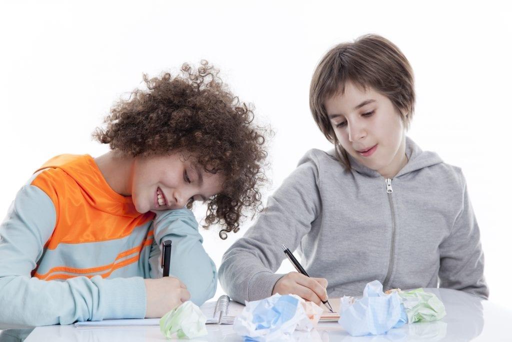 Deux jeunes qui écrivent avec des boulettes de papier
