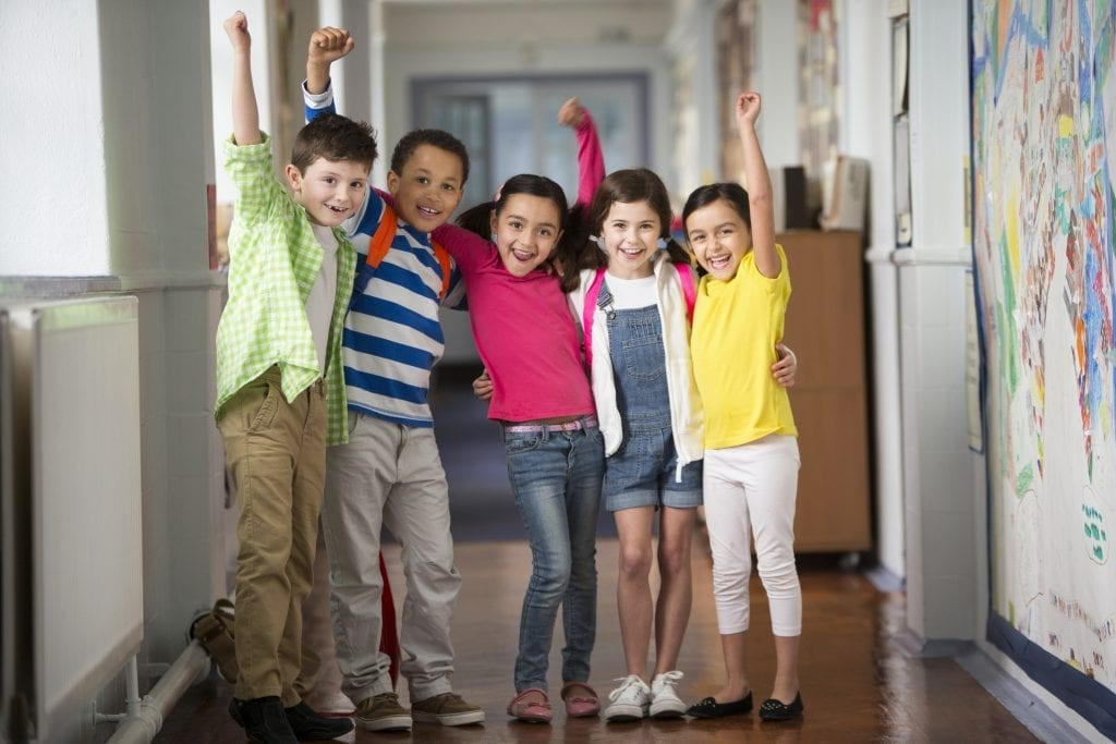 Groupe de jeunes du primaire levant le poing en l'air