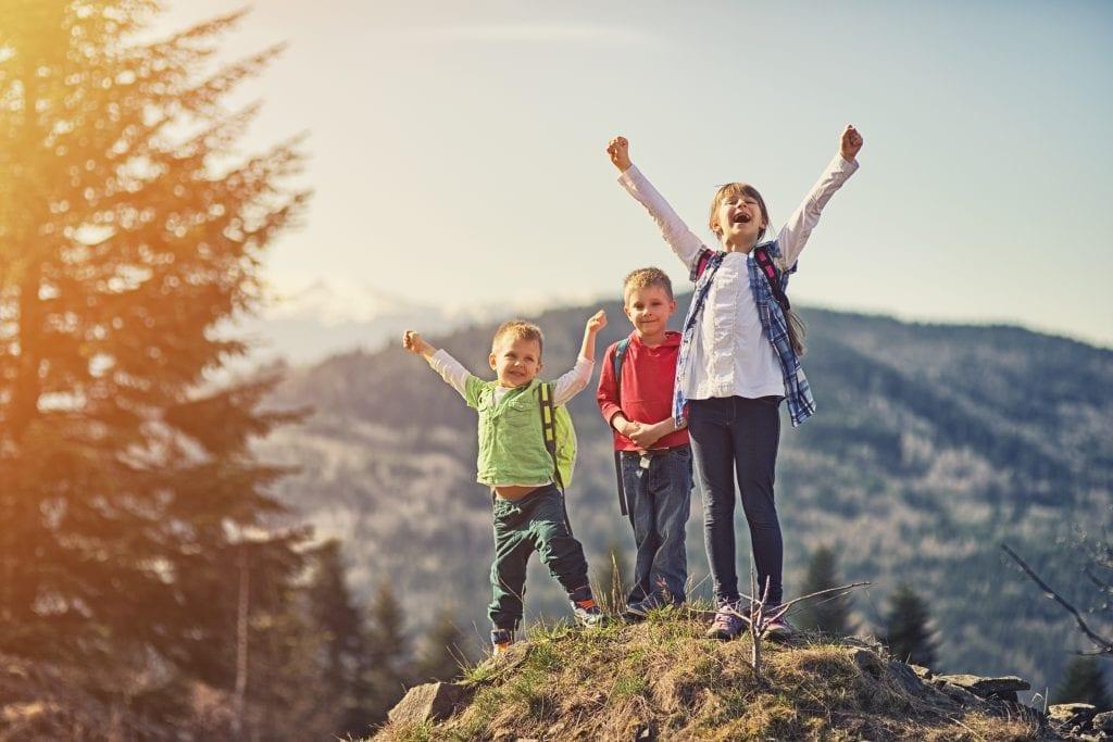 Trois jeunes fiers d'avoir atteint le sommet dela montagne