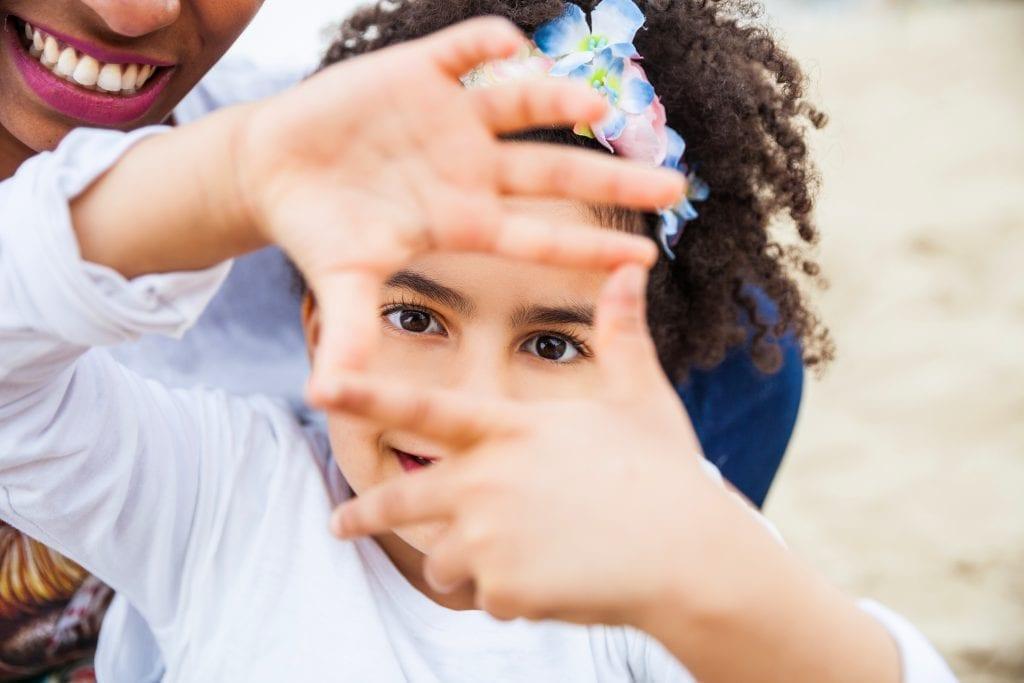 Jeunes filles qui encadre ses yeux avec ses doigts
