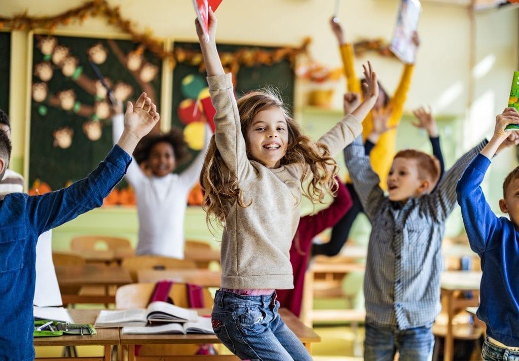 Élèves du primaire qui sautent dans une classe