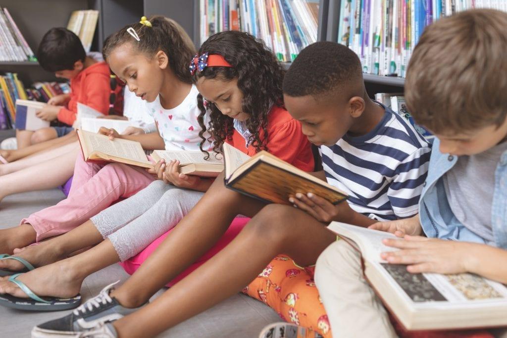 Élèves du primaire qui lisent à la bibliothèque