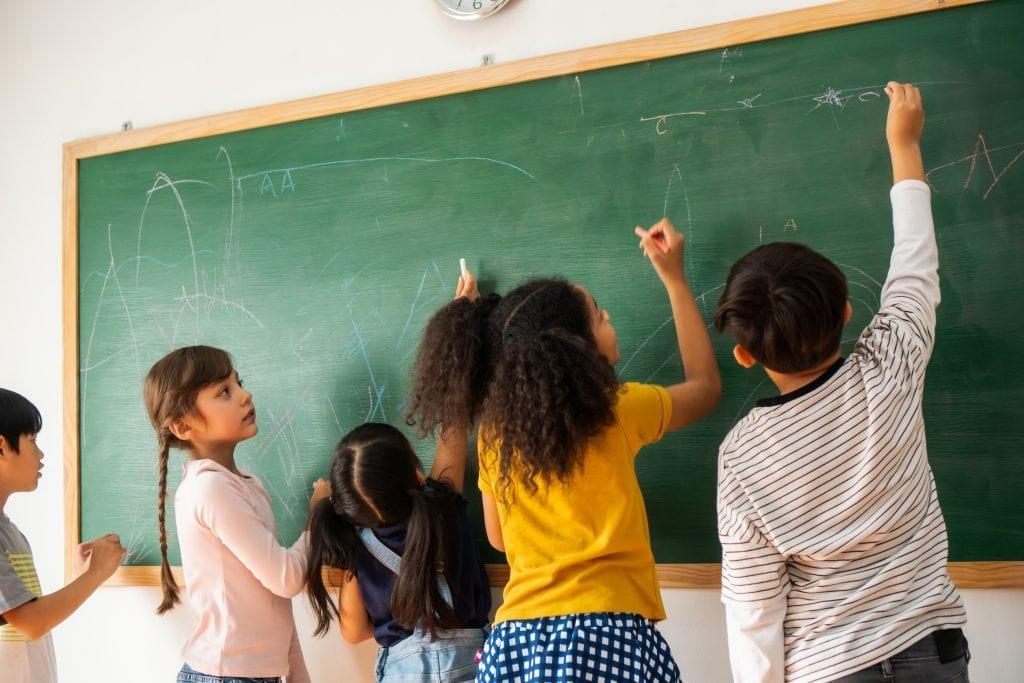 Groupe d'élèves du primaire qui fait un remue-méninges sur un tableau