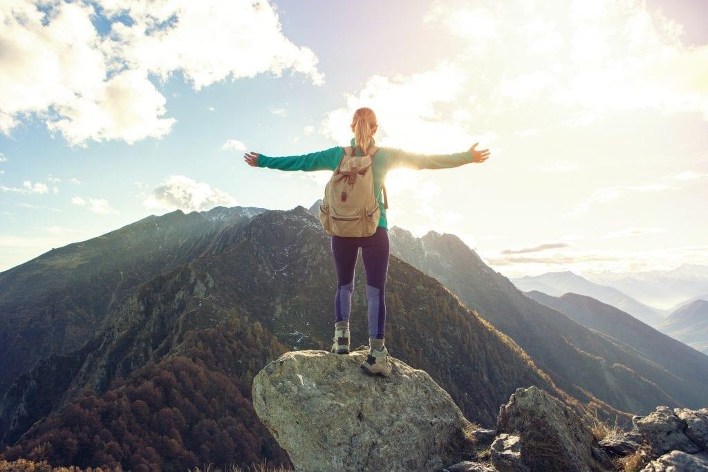 Jeune femme au sommet d'une montagne