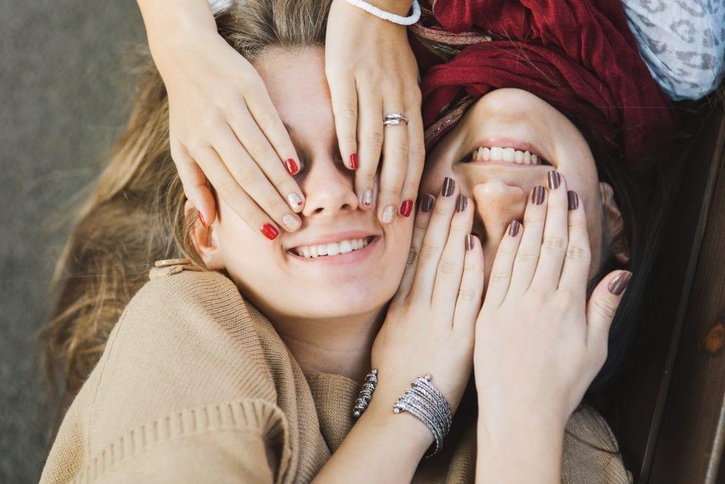 Deux adolescentes qui se cachent les yeux avec leurs mains