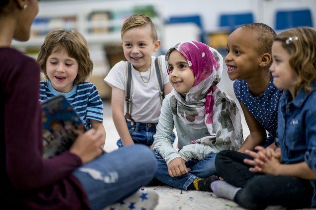 Groupe de jeunes élèves qui écoutent leur enseignante